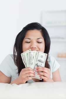 Женщина закрывает глаза, когда она держит несколько долларовых купюр