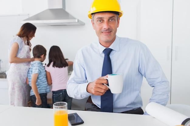 父親がハードホームを着て家庭でコーヒーを飲む