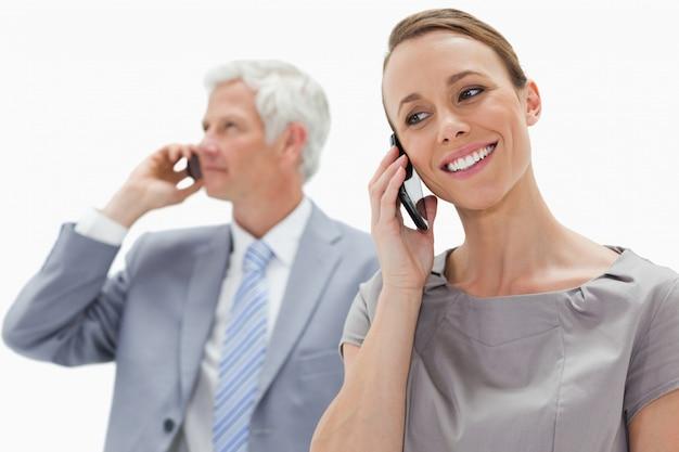 白い髪のビジネスマンと電話をかける笑顔の女性のクローズアップ