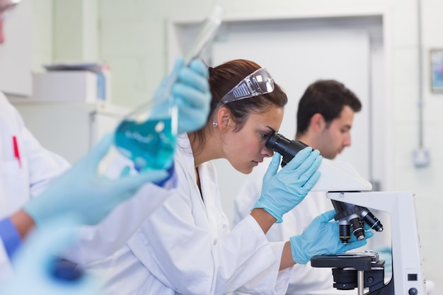 Занятые исследователи, работающие над экспериментами в лаборатории