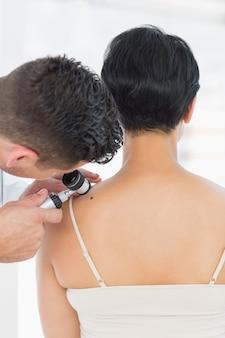 女性のモルを調べる皮膚科医