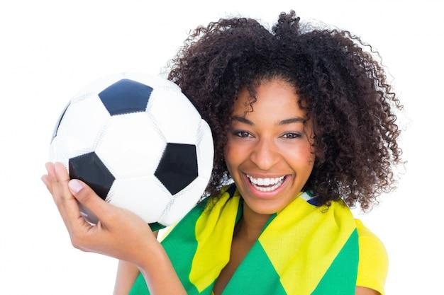 ブラジルの旗がカメラで笑っているサッカーファン