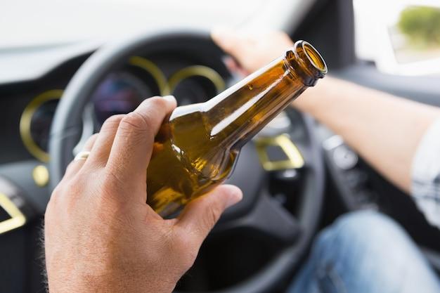 運転中にビールを飲む男