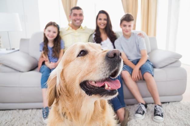 Собака, сидящая с семьей дома