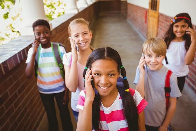 学校の廊下で携帯電話を使用している学校の子供たち