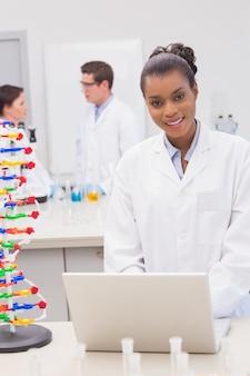 Улыбаясь ученый, используя ноутбук, когда коллеги говорят вместе