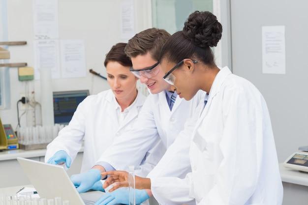 Ученые, смотрящие на ноутбук вместе