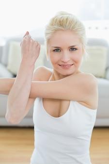 フィットネススタジオで手を伸ばしているスポーティな女性