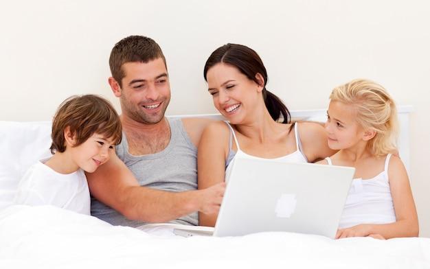 ベッドでラップトップを使用している親子