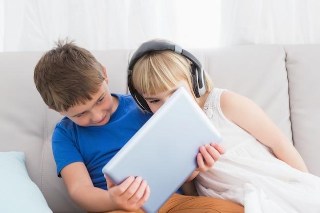 Братья и сестры, используя наушники и планшет, сидящие на диване