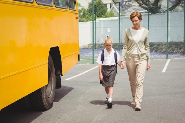 彼女の娘を学校バスに歩いている母