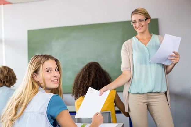 Преподаватель, вручающий бумагу студенту в классе