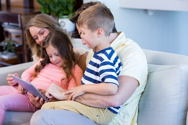 Семья на диване вместе с планшетным пк