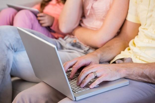 Семья на диване с планшетным пк и ноутбуком