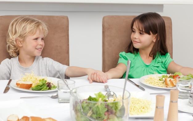 かわいい兄と妹が昼食前に手を握っている