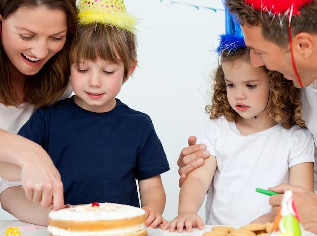 母と息子が一緒に誕生日のケーキを切る