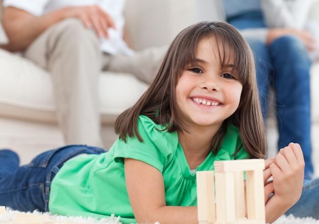 リビングルームでドミノで遊んでいるかわいい女の子