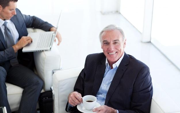 Старший бизнесмен, пить кофе и ждать собеседования