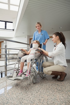 彼女の子供の隣に身を置いている看護婦が車椅子に座っている母親