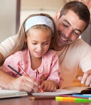 彼女の娘の宿題を助けるハンサムな父