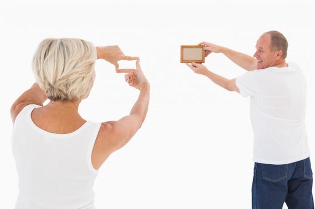 写真のフレームを掛けている熟年のカップル
