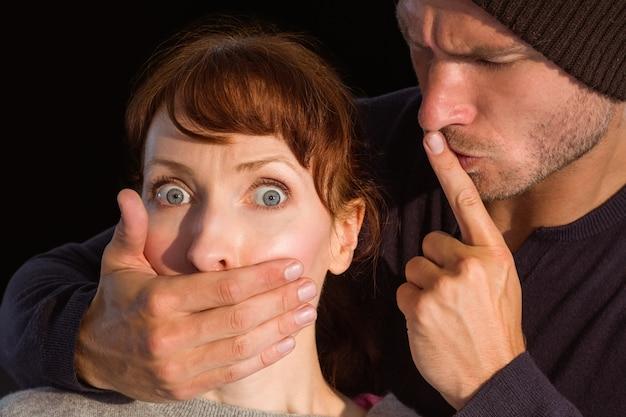 Человек, схватив женщину за рот