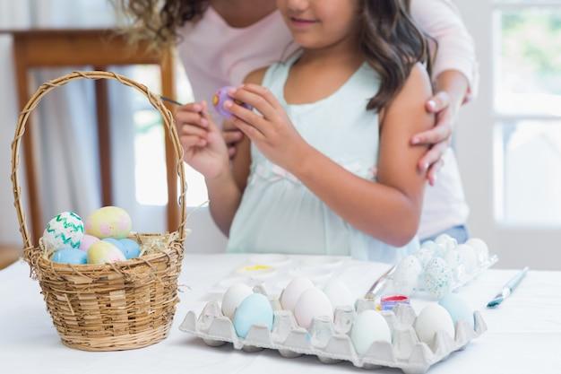 Счастливая мать и дочь, рисование пасхальных яиц
