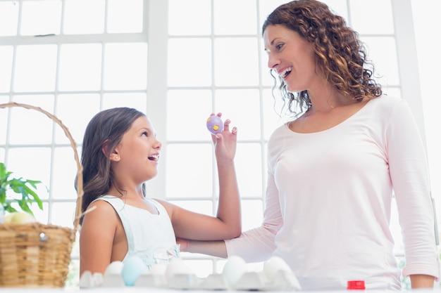 Счастливая девушка показывает пасхальное яйцо матери