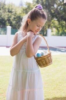 Маленькая девочка, собирающая пасхальные яйца