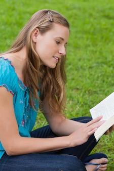 本を読んでいる間に公園に横たわっている若い魅力的な女の子