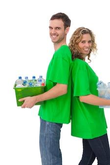 リサイクル可能なボックスを持ち、背中合わせに立っている明るい活動家