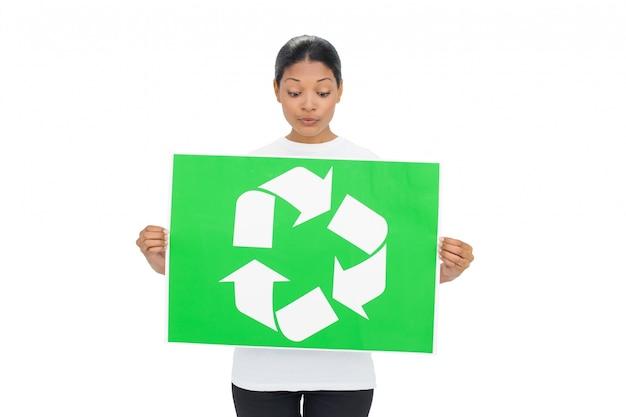 リサイクルのサインを持っている好奇心の若い女性