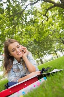 電話で草の上に横たわる若い幸せな学生