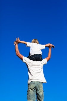 父親の肩に座っている息子