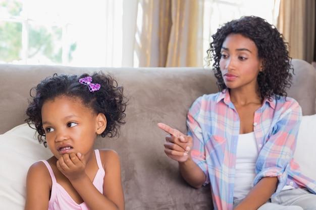 かわいい娘を叱るソファーに座っているかなりの母