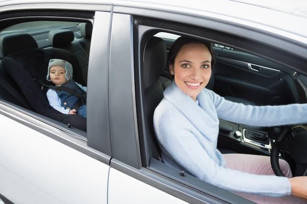 Мать водит с ребенком на автокресло