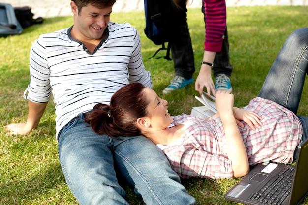 草の上に横たわる明るい学生のカップル