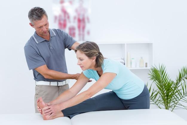 彼の患者のストレッチを助ける理学療法士