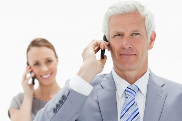 笑顔の女性と電話で白髪のビジネスマンのクローズアップ