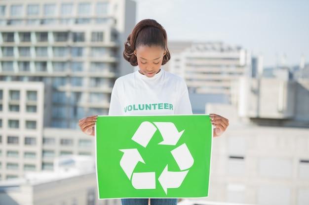 かなりのボランティアの女性がリサイクルのサインを持っています