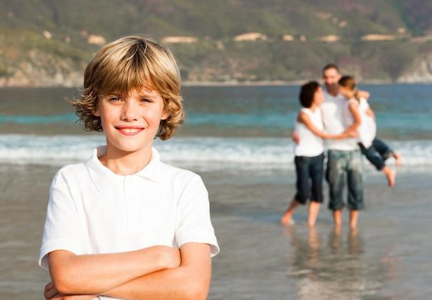 Симпатичный мальчик на пляже с родителями и его сестрой в фоновом режиме