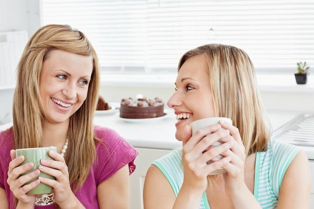 Восхищенные женщины-друзья, которые держат чашку кофе у себя дома