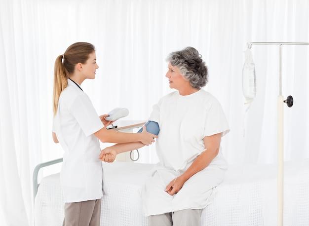 Медсестра, принимающая кровяное давление своего пациента