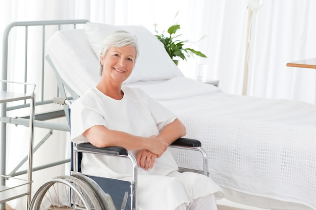 カメラを見て彼女の車椅子のシニアの女性