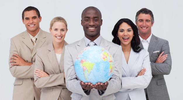 Афро-американский бизнесмен, держащий земной шар со своей командой