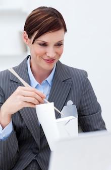 箸で中国料理を食べるビジネスマン