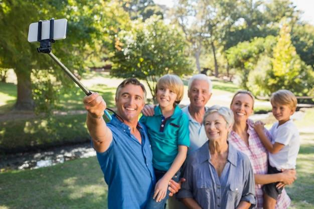 公園でセルフスティックを使っている幸せな家族