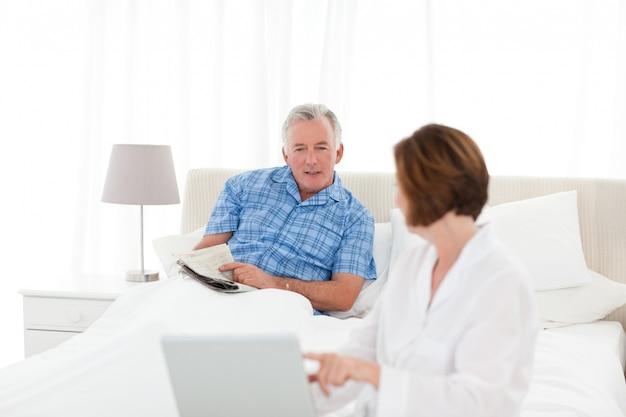 Пожилые люди говорят в постели