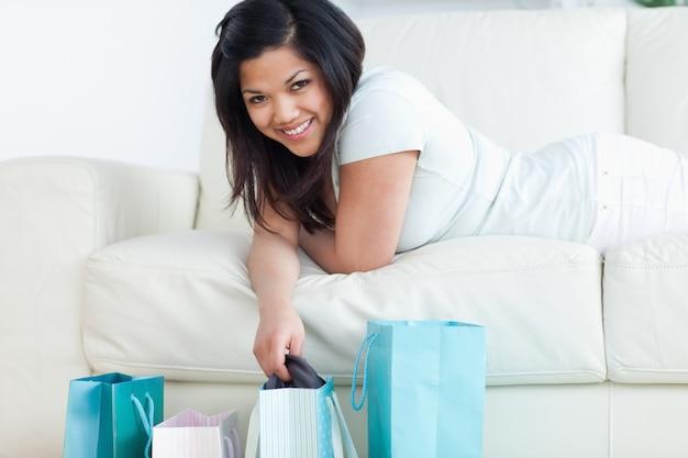 Женщина, лежа на диване, удерживая одежду из сумки