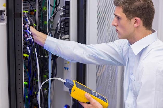 Серьезный техник, использующий цифровой анализатор кабеля на сервере